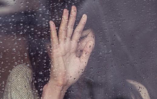 femme derrière une vitre, la main devant son visage